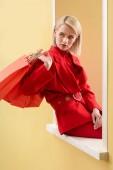 Fényképek fiatal, divatos nő piros ruha, piros bevásárló táskák, dekoratív ablakban ül