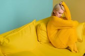 Fotografie side view of young blond woman in yellow sweater and tights sitting on yellow sofa on blue backdrop