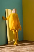 Fotografie back view of blond woman in yellow sweater and tights standing at mirror