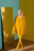 beautiful pensive blond woman in yellow sweater and tights standing at mirror