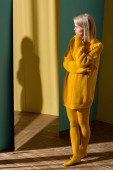 attractive blond woman in yellow sweater and tights standing at mirror
