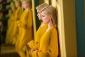 Fotografie selektiven Fokus der blonden Frau in gelben Pullover und Strumpfhosen am Spiegel mit ihr Spiegelbild drin stehen