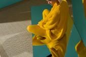 Fotografie Schuss von Frau im gelben Pullover und Strumpfhosen auf Spiegel mit Reflexion drin sitzen abgeschnitten