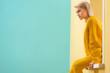 side view of stylish woman in yellow sweater and tights sitting on decorative window