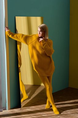 stylish blond woman in yellow sweater and tights standing at mirror