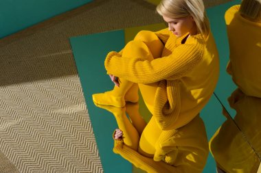 side view of woman in yellow sweater and tights sitting on mirror with reflection in it