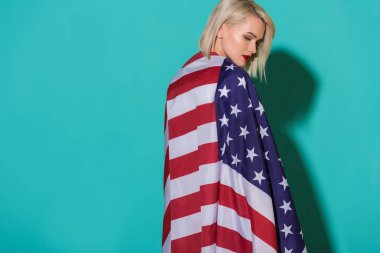 back view of young woman with american flag on blue backdrop, celebrating 4th july concept
