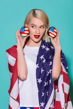 portrait of young  woman with american flag and cupcakes on blue backdrop, celebrating 4th july concept