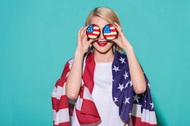 obscured view of cheerful woman with american flag and cupcakes on blue backdrop, celebrating 4th july concept