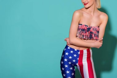 partial view of smiling woman in top and leggings with american flag pattern posing on blue background