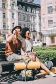 Photo multicultural couple of tourists with backpacks and mats resting on bench