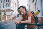 Fotografie young smiling male tourist with coffee cup pointing by finger to african american girlfriend