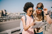 multiethnic young couple of tourists looking at map