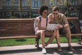 Fotografie multiethnic couple of young tourists looking at map and sitting on bench