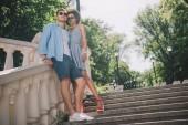 Fotografia Inquadratura dal basso di eleganti coppie multiculturali che stanno sulle scale nel parco
