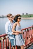 multikulturális elegáns pár napszemüveg állandó híd a folyón