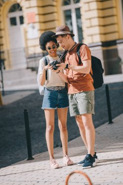 multiethnic couple of young tourists looking photographs on camera screen