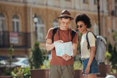 young male traveler pointing at map to african american girlfriend standing near