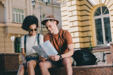 smiling interracial couple of tourists with map looking for destination
