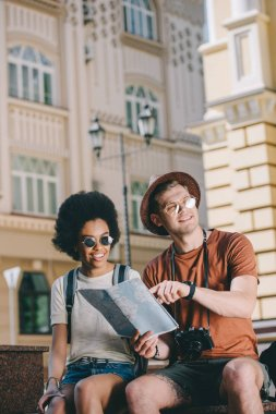 young male traveler pointing at map to african american girlfriend