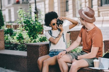 young female traveler taking picture of boyfriend on camera