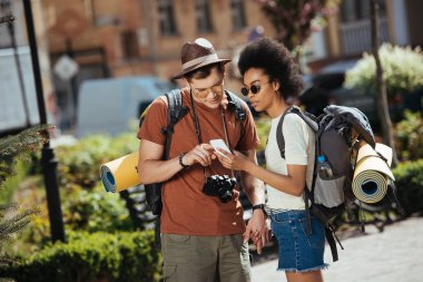 young couple of tourists with smartphone looking for destination