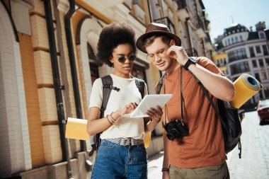 african american female traveler in sunglasses holding digital tablet and her boyfriend looking for destination