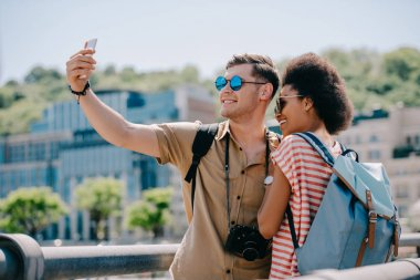 multiethnic couple of travelers in sunglasses taking selfie on smartphone