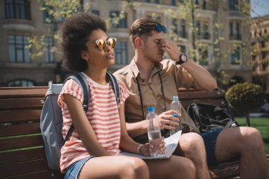 tired interracial couple of travelers with bottles of water and map sitting on bench