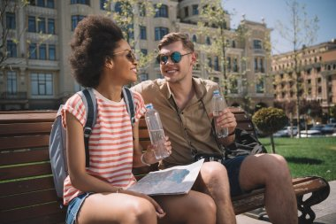 multicultural couple of travelers with map and bottle of water resting on bench
