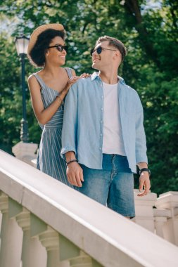 smiling multiethnic couple in sunglasses standing on stairs in park