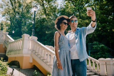 low angle view of smiling multiethnic couple in sunglasses taking selfie on smartphone in park