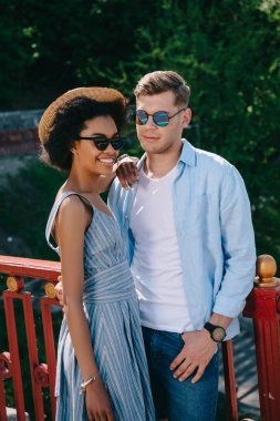 smiling african american woman in sunglasses standing with boyfriend