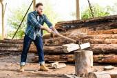 lumberjack in checkered shirt chopping log at sawmill