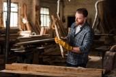 vousatý carpenter v ochranné rukavice, práci se dřevem na pile