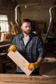 Tesař v ochranné rukavice, práci s dřevěné prkno na pile