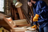 vousatý řemeslník v ochranné rukavice a brýle vrtání dřevěné prkno na tesařské