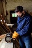 řemeslník v ochranné brýle a rukavice pomocí bruska na pily