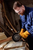 Fotografie vousatý řemeslník v ochranné brýle a rukavice pomocí bruska na pily
