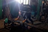 Fotografie dělník v ochranné rukavice stroj tlačí na pilu