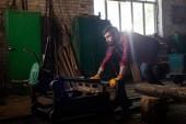 Seitenansicht des Arbeiters in Schutzhandschuhen drücken Maschine im Sägewerk