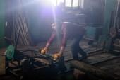 Fotografie vousatý dělník v ochranné rukavice stroj tlačí na pilu
