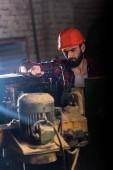 Fotografie pracovník v ochranné přilbě opravy obráběcích strojů na pile