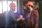 Fotografie side view of bearded carpenters in protective helmets shaking hands at sawmill