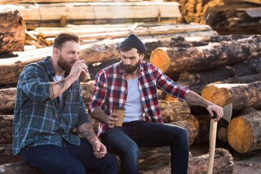 two bearded loggers sitting with disposable cups of coffee and axe
