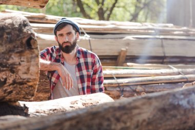 bearded lumberjack in checkered shirt standing at sawmill