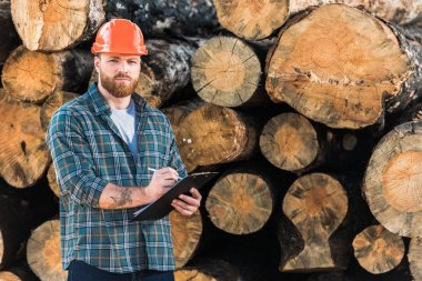 lumberjack with tattooed hand in protective helmet writing in clipboard on logs background