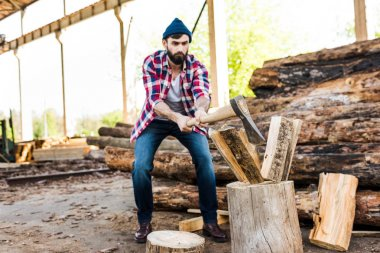 front view of bearded lumberjack in checkered shirt chopping log at sawmill