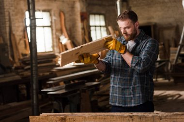 bearded carpenter in protective gloves checking wooden plank at sawmill