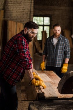 bearded carpenter in safety googles using machine saw and partner standing behind at sawmill